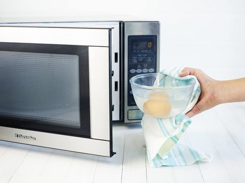 Eggs being placed in a microwave