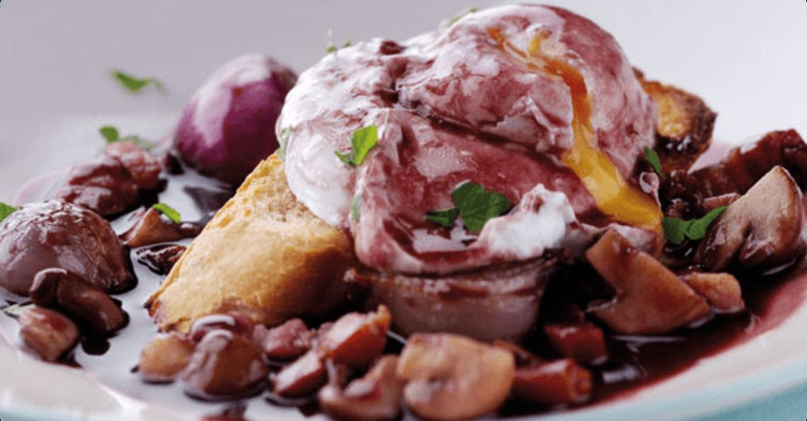 Poached eggs in red wine with smoked bacon and onions